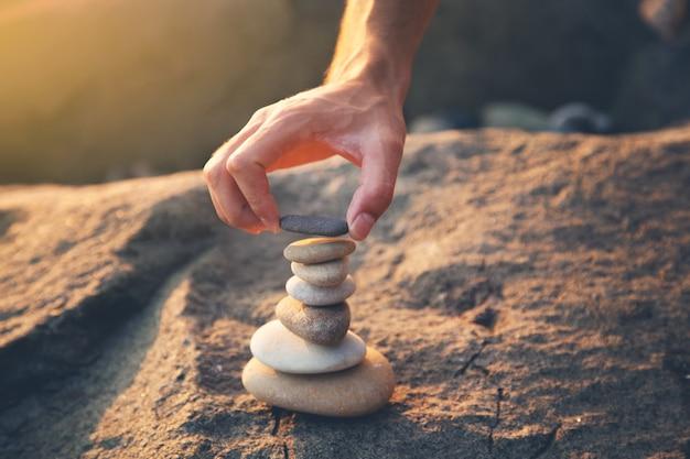 Man mano torre di pietra sulla spiaggia