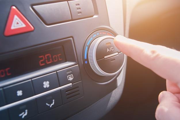 La mano dell'uomo accende l'aria condizionata in macchina. conducente che accende il sistema di climatizzazione dell'auto. viaggiare in macchina. vista ravvicinata con il fuoco selettivo.