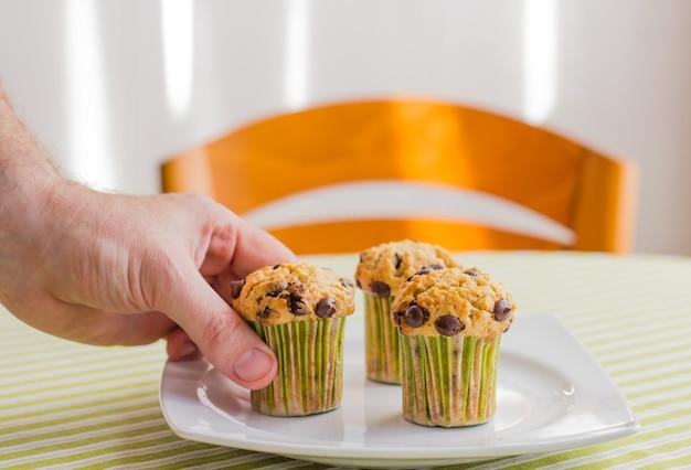 Mano dell'uomo che prende un delizioso muffin con gocce di cioccolato a colazione in una tovaglia a strisce verdi