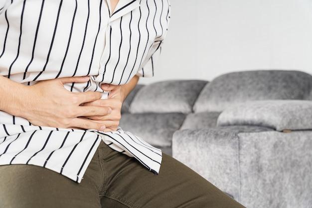 Mano dell'uomo che tocca lo stomaco che soffre mentre è seduto sul divano