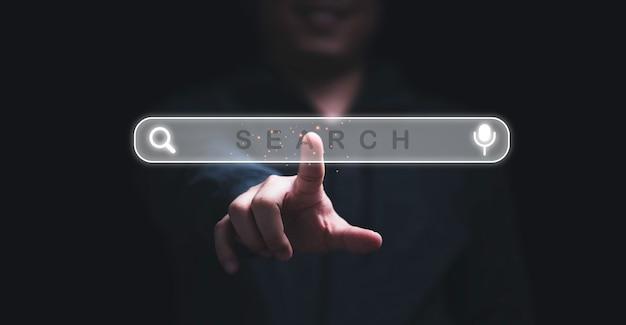 Mano dell'uomo che tocca l'icona di ricerca dello screening virtuale per il concetto di motore di ricerca web.