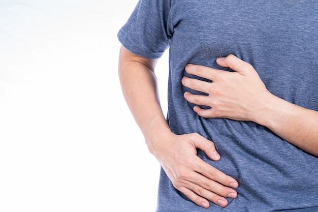 Man mano che tocca la vita o la posizione del fegato isolato muro bianco.