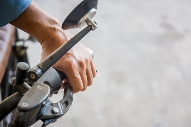 Mano dell'uomo ha spento la frizione su una motocicletta, mano di un motociclista che tiene un freno della motocicletta