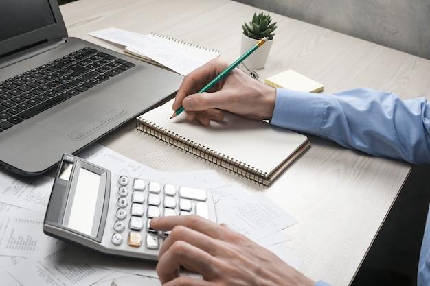 Man mano utilizzando la calcolatrice e la scrittura prendere nota con calcolare i costi e le tasse in ufficio a casa. imprenditore facendo alcune scartoffie sul posto di lavoro