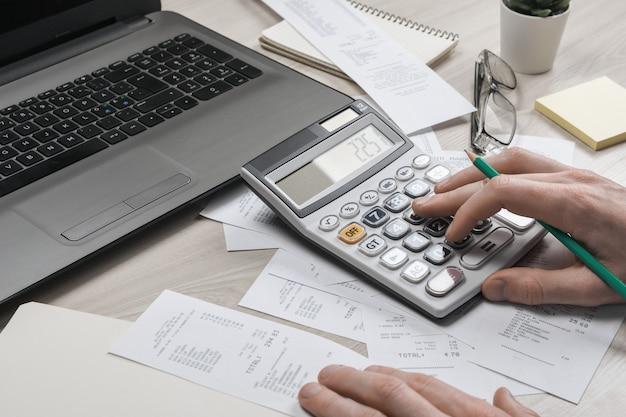 La mano dell'uomo facendo uso del calcolatore e della scrittura prende nota con calcola circa l'ufficio delle tasse e di costo a casa.