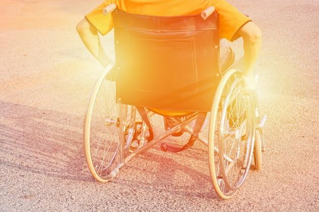 Mano di uomo sulla ruota di sedia a rotelle sulla strada nel parco della città