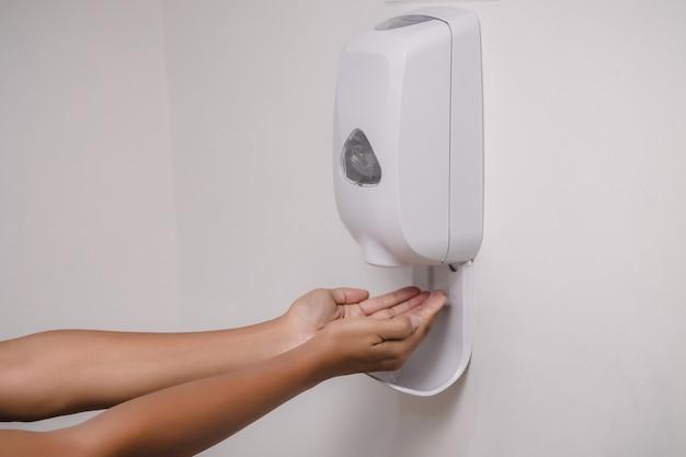 Mano dell'uomo con gel antibatterico dalla macchina automatica di sanificazione appesa al concetto di assistenza sanitaria della parete dell'edificio
