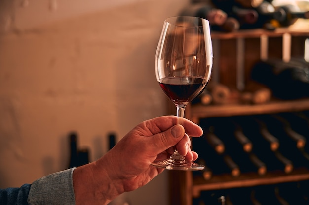 Man mano con bicchiere di bevanda alcolica e portabottiglie su sfondo sfocato