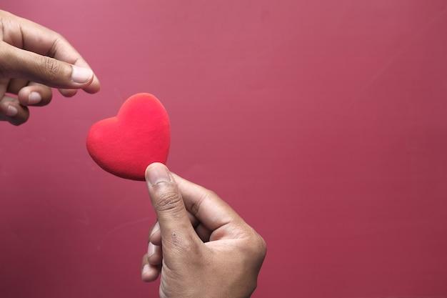 Mano dell'uomo con il cuore. il concetto di prendersi cura della salute.