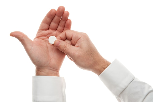 Man mano con una grande pillola bianca isolata su sfondo bianco. camicia bianca, stile business. medicamento e integratore alimentare per l'assistenza sanitaria. industria farmaceutica. farmacia.