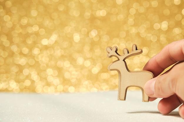 Mano d'uomo con ornamento natalizio in legno a forma di renna su sfondo bianco e oro lucido sfocato