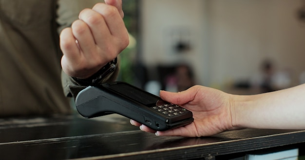 Mano dell'uomo con smartwatch utilizzando il terminale per il pagamento in caffetteria, transazione non in contanti, vista laterale. concetto di pagamento non in contanti. pos-terminale sul tavolo su sfondo nero.
