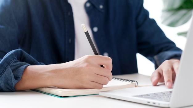 Man mano che scrive sul notebook mentre si utilizza il computer portatile
