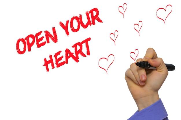 Man mano che scrive apri il tuo cuore con un pennarello sulla lavagna trasparente. isolato su bianco.