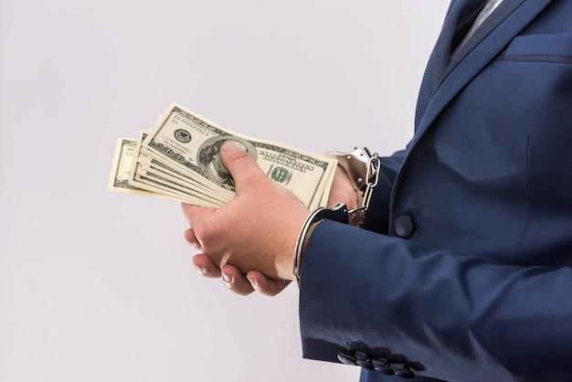 Uomo in manette che tengono banconote in dollari isolate, primo piano. arresto