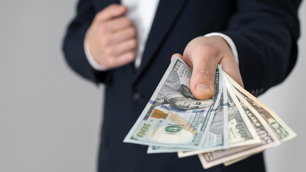 Uomo che passa un mucchio di banconote in dollari