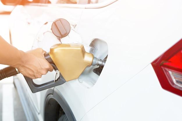 Maniglia dell'uomo che riempie l'auto di carburante alla stazione di rifornimento