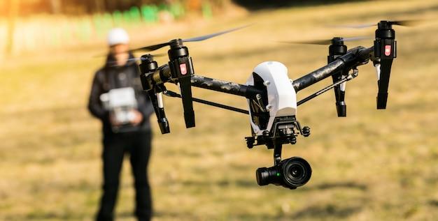 Uomo che maneggia il drone in natura, concentrato sul drone