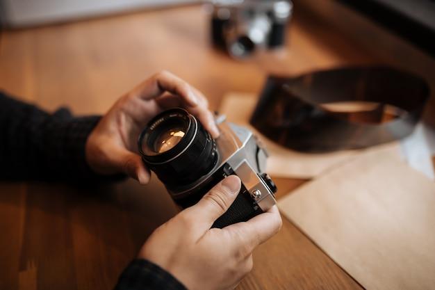 Le mani dell'uomo regola la retro macchina fotografica dell'obiettivo su una tavola di legno