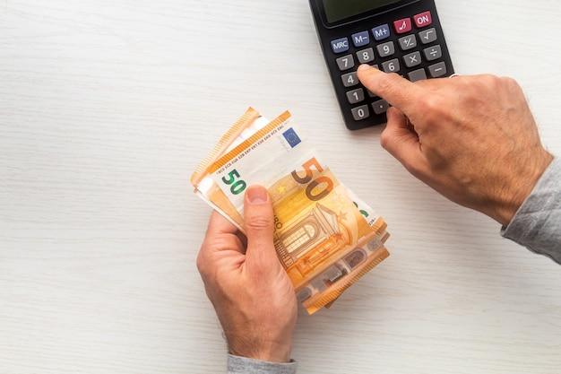 L'uomo passa il conteggio delle banconote in euro denaro contante e calcolatrice sul tavolo bianco