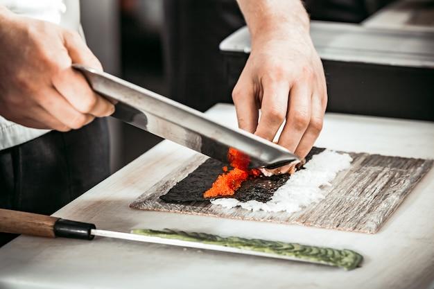 L'uomo passa il taglio di caviale sullo strato di alghe e riso