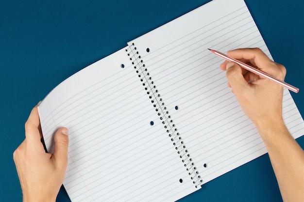 Le mani dell'uomo tengono le pagine aperte del taccuino con la matita, lo scolaro che fa i compiti, la scrivania del lavoratore di ufficio laici piatta. blocco note vuoto sul tavolo