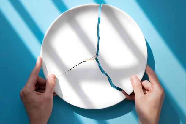 Equipaggi le mani che tengono un piatto bianco rotto su fondo blu, luce solare. metafora di divorzio, relazioni, amicizie, crack nel matrimonio