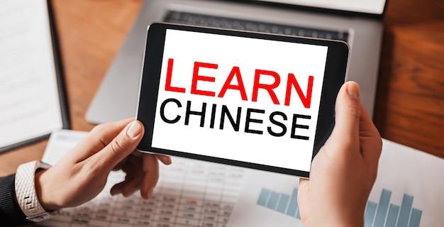 Mani dell'uomo che tengono compressa con testo impara il cinese sul posto di lavoro
