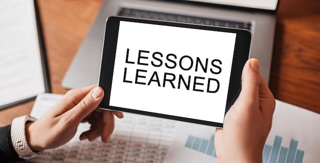 Mani dell'uomo che tengono tablet con testo lezioni apprese sul posto di lavoro. uomo d'affari che lavora alla scrivania con documenti. concetto di studio e istruzione