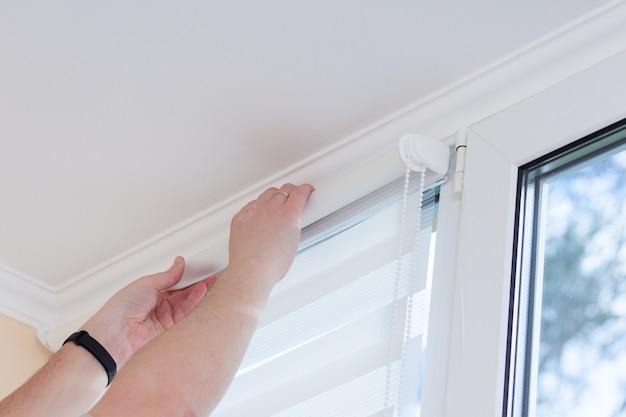 Equipaggi le mani che installano il sistema di giorno e notte del rullo a rulli della finestra.