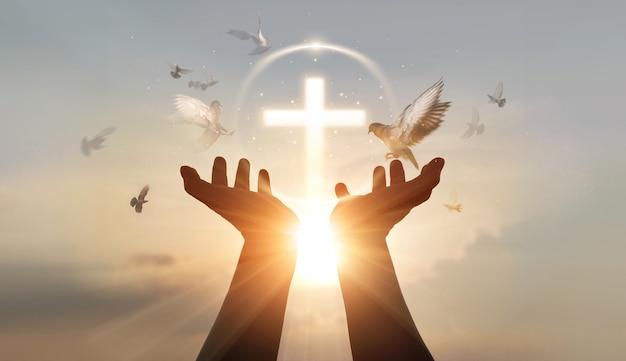 Mani dell'uomo palmo verso l'alto pregando e adorando la terapia eucaristica della croce benedicono dio aiutando la speranza e la fede