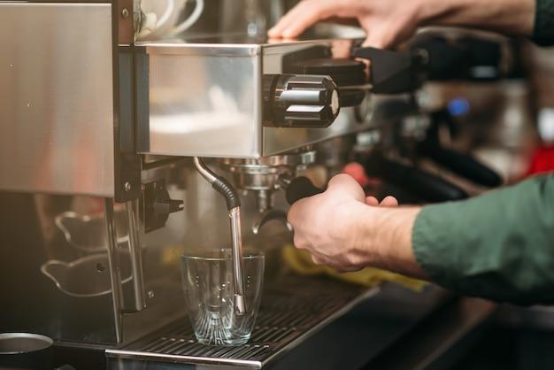 Mani dell'uomo versa il caffè da una macchina per il caffè.