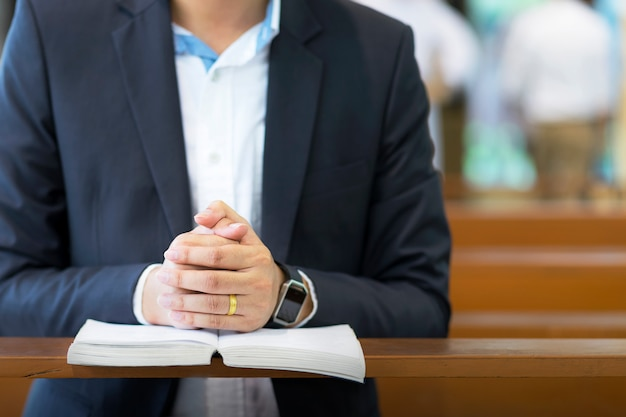 Equipaggi le mani che pregano su una bibbia santa in chiesa per il concetto di fede, la spiritualità e la religione cristiana.