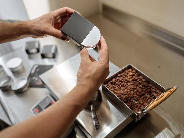 Mani dell'uomo che mettono un barattolo di caffè in metallo nella scatola nera