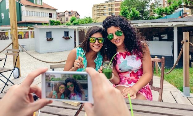L'uomo passa la foto con lo smartphone a due giovani donne felici con occhiali da sole che tengono frullati di verdure verdi all'aperto