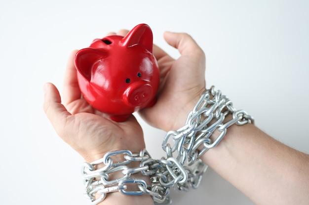 Nelle mani dell'uomo legate dal concetto di dipendenza da credito del porcellino salvadanaio di maiale rosso a catena