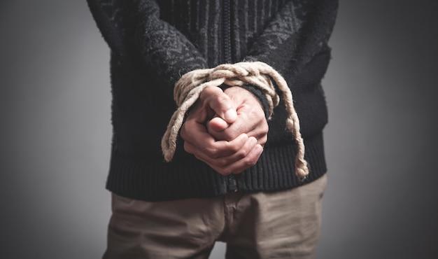 Mani dell'uomo legate da una corda. reclusione