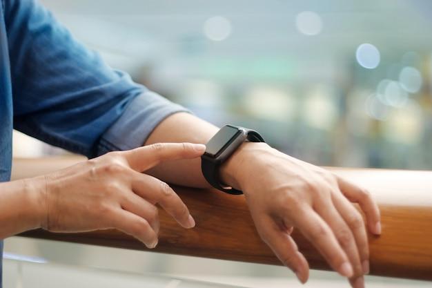 Mani dell'uomo toccando l'orologio