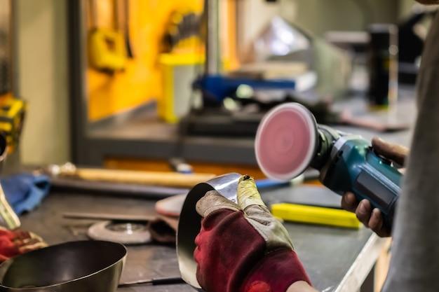 Man mano il trattamento di parti metalliche di hardware in un'officina con smerigliatrice angolare. operaio metallurgico maschio che lucida e finalizza un pezzo di armatura medievale.
