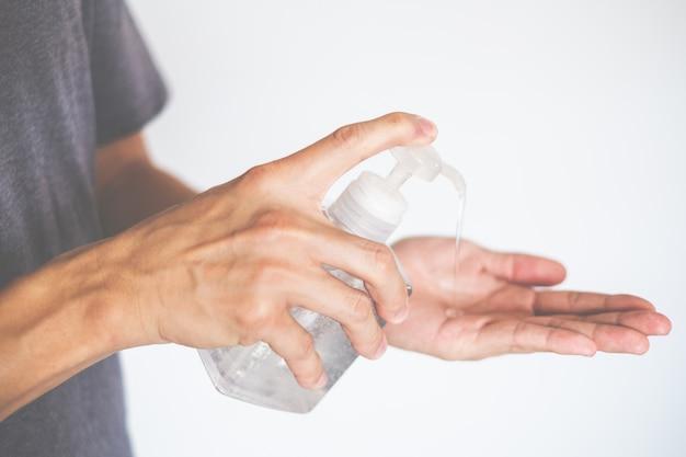 Man mano usando il distributore di gel disinfettante per mani