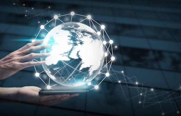 Equipaggi le mani facendo uso della sfera del mondo con lo smartphone collegato