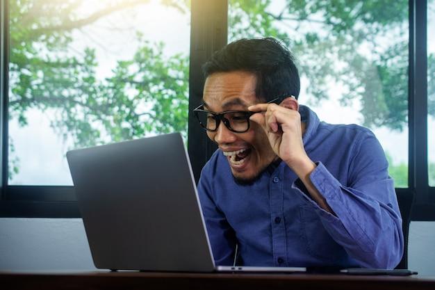 L'uomo felice eccitato commercio di profitto online, uomo d'affari che utilizza il computer felice così eccitato affari di profitto