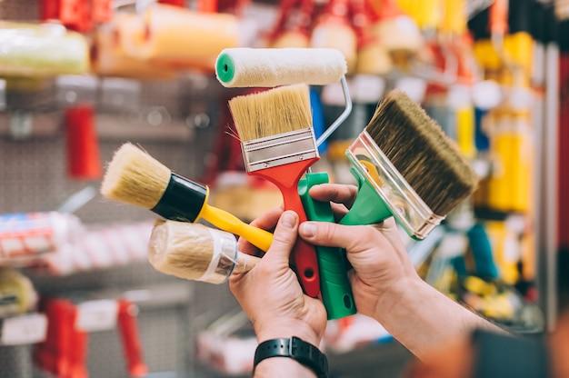 Un uomo in un negozio di ferramenta tiene in mano un set di pennelli e rulli per pittura e decorazioni.