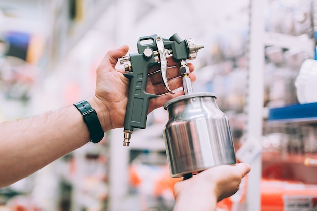 Un uomo in un negozio di ferramenta tiene una pistola a spruzzo per dipingere un'auto.