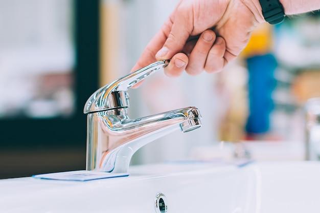 Un uomo in un negozio di ferramenta sceglie un rubinetto per il lavandino e il lavabo.