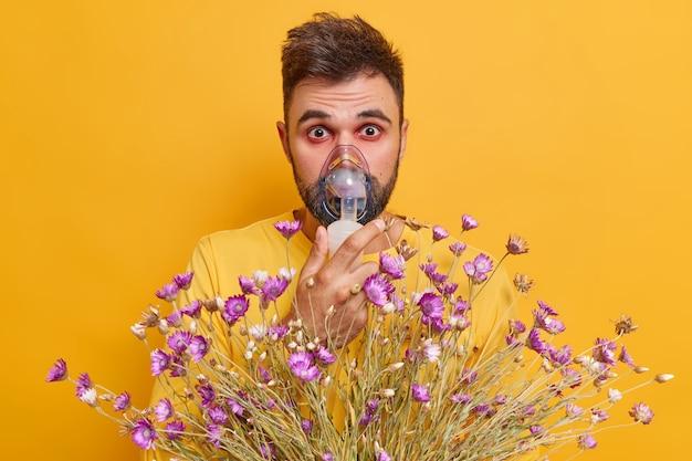 Uomo ha asma bronchiale soffre di mancanza di respiro attacco respiratorio indossa maschera nebulizzatore reagisce al polline ha allergia ciugh gonfiore rosso occhi isolati su parete gialla