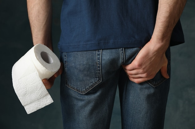 L'uomo ha la diarrea. l'uomo tiene la carta igienica