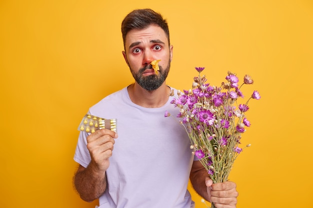 L'uomo ha un tovagliolo nella narice soffre di rinite allergica e congiuntivite tiene un mazzo di fiori di campo e pillole per curare la malattia