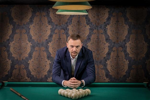 Un uomo ha messo le palline sul tavolo da biliardo ed è pronto per giocare