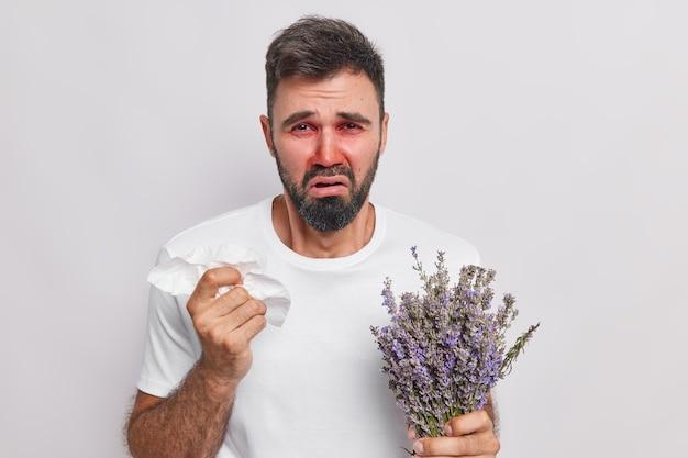 L'uomo ha il naso che cola tiene il fazzoletto non riesce a smettere di starnutire ha allergia alla lavanda indossa una maglietta casual occhi rossi pruriginosi e naso isolato sul muro bianco. reazione allergica